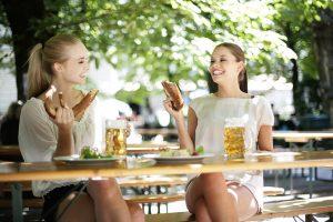 Biergärten Wien: Zwei junge Frauen sitzen im Biergarten, trinken Bier und essen Brezln.