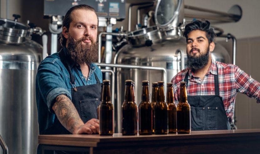 Zwei junge, gutaussehende Braumeister, die in einer Craft Beer Brauerei verschiedene Sorten präsentieren. Craft Beer Wien.
