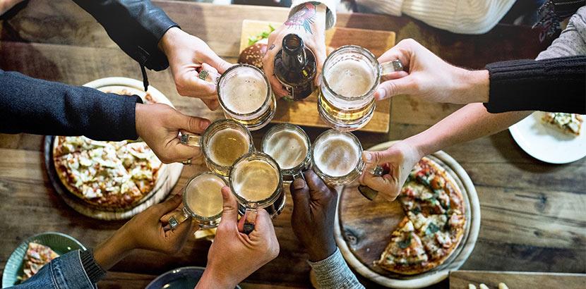 Gruppe von Männern, die über einem Tisch voller Snacks mit verschiedenen Sorten Craft Beer anstoßen. Craft Beer Wien.