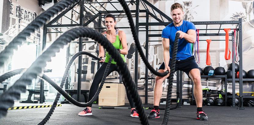 Junge Frau und junger Mann im Fitnessstudio beim battle rope. Crossfit Wien.