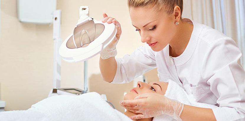 Junge blonde Hautärztin, die eine Patientin untersucht. Welcher Arzt wofür?