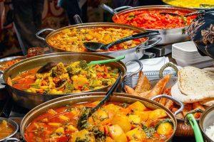 Indische Restaurants Wien: Ein Tisch voller bunter indischer Gerichte wie Curry, Naan und Samosas.