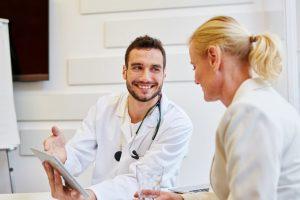 Junger Internist, der ein Gespräch mit einer blonden Patientin führt und sie dabei freundlich anlächelt. Internist Wien.