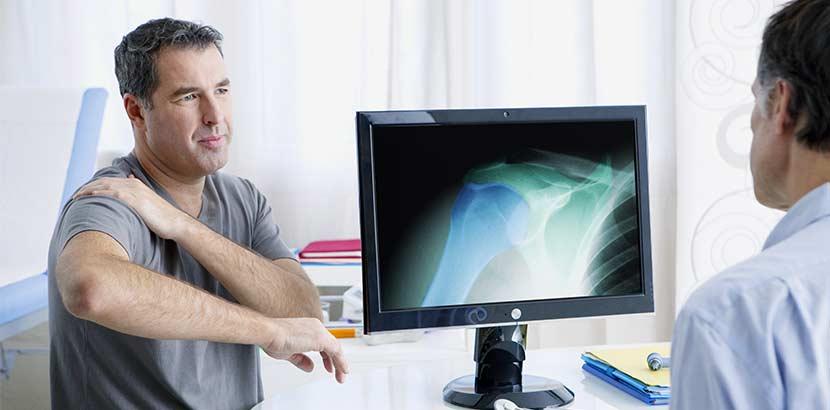 Mann beim Arzt wegen Schmerzen durch Kalkschulter