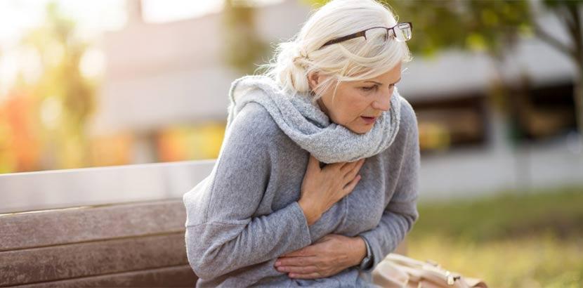 Frau in mittlerem Alter, die auf einer Bank sitzt und plötzlich Atemnot und Brustschmerzen bekommt. Kardiologe Wien.