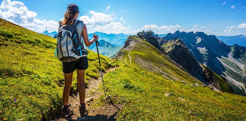 Junge Frau in Wander-Ausrüstung, die im Gebirge unterwegs ist. Neurodermitis Erwachsene.