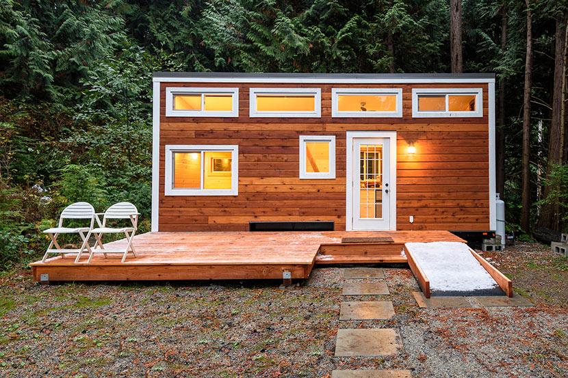 Ein Tiny House aus Holz steht im Wald.