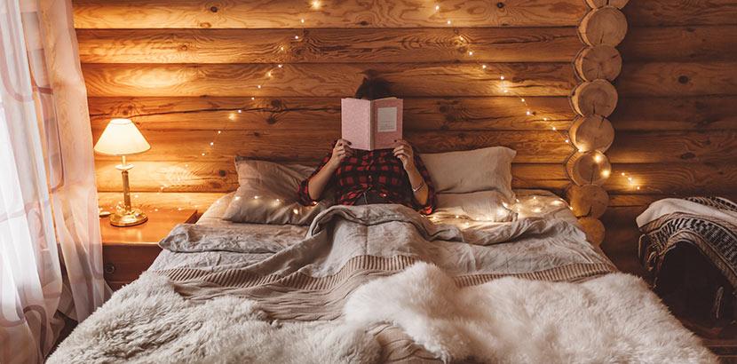 Eine Frau sitzt in ihrem Tiny House aus Holz und liest entspannt ein Buch. Im Minihaus lässt es sich perfekt abschalten.
