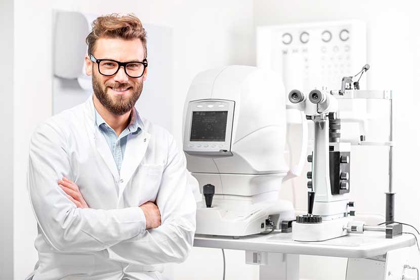 Augenarzt Wien: Gutaussehender junger Facharzt für Augenheilkunde, der lächelnd vor seinen Untersuchungsgeräten steht.