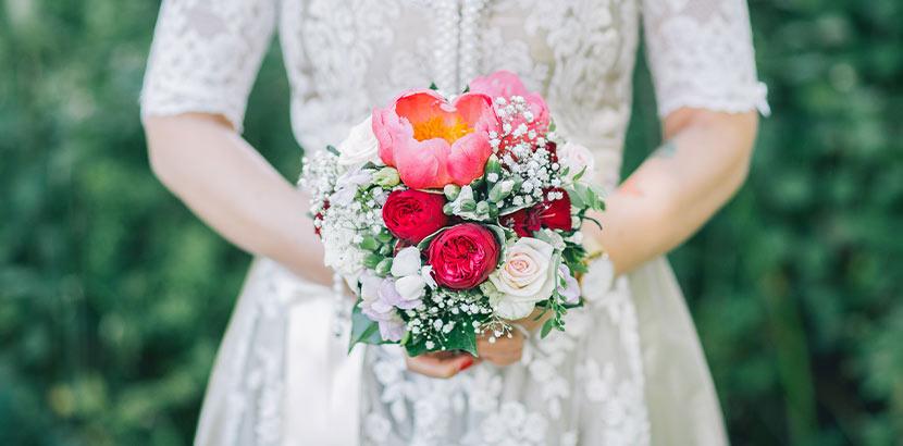 Eine Frau hält einen Brautstrauß mit Rosen, Schleierkraut und einer Pfingstrose.