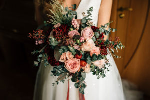 Eine Braut hält einen romantischen, modernen Brautstrauß mit roten Blumen
