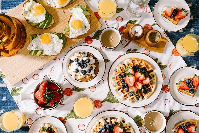 Frühstück Salzburg: Ein Frühstückstisch mit Pancakes, Waffeln, Spiegeleiern, Kaffee und frischen Früchten