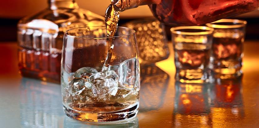 Whisky-Glas, in das gerade Whisky als Geschenk für Papa eingeschenkt wird.