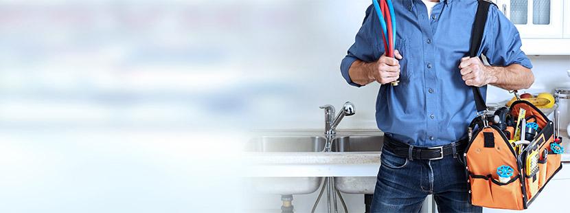 Installateur mit Werkzeugtasche vor blauem Hintergrund. Installateur Wien.