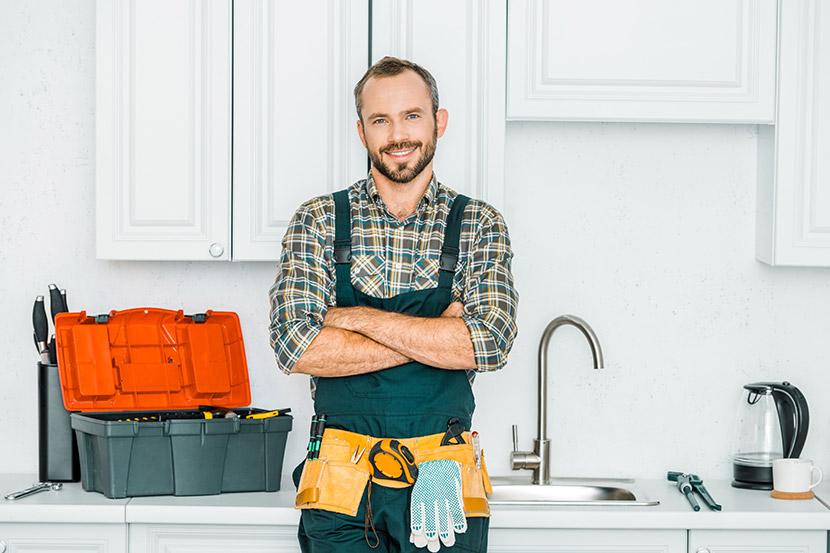 Gutaussehender Installateur mit Werkzeuggürtel in einer Küche. Installateur Wien.