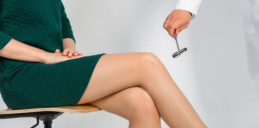 Neurologe Wien, der die Reflexe einer jungen Frau in einem kurzen grünen Kleid testet.