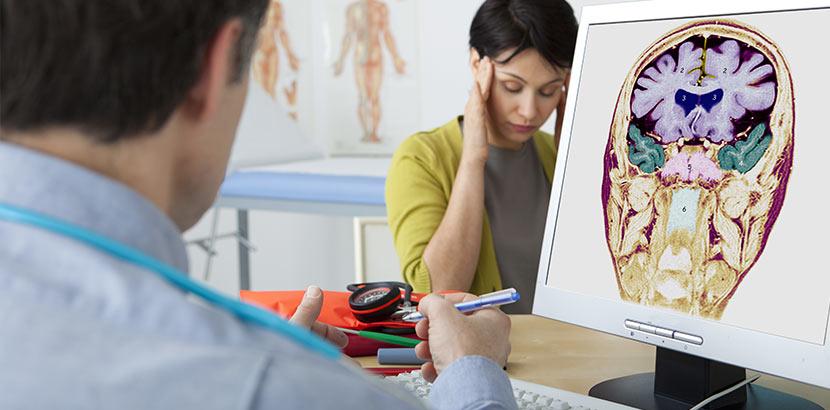 Junge Frau mit dunklen kurzen Haaren, die von einem Neurologen ihre Untersuchungsergebnisse mitgeteilt bekommt. Neurologe Wien.