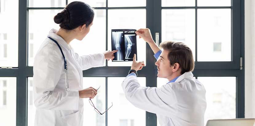 Ein Orthopäde und eine Orthopädin, die über eine Röntgenaufnahme diskutieren.