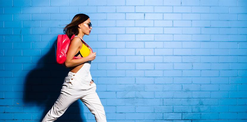 Junge Hipster-Frau mit pinkem Turnbeutel vor einer blauen Wand.