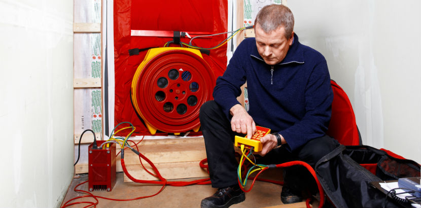 Blower-Door-Test: Ein Handwerker misst die Luftdichte eines Gebäudes.