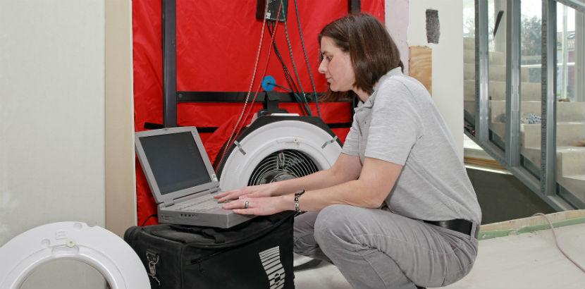 Blower-Door-Test: Eine Technikerin misst die Luftdurchlässigkeit eines Gebäudes.