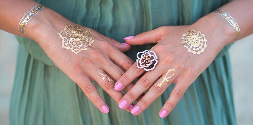 Festival-Pacliste: eine Frau mit goldenen Henna-Tattoos und rosa Fingernägeln