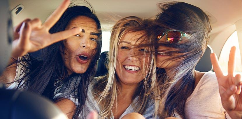 Festival-Packliste: Drei Frauen fahren im Auto zu einem Festival