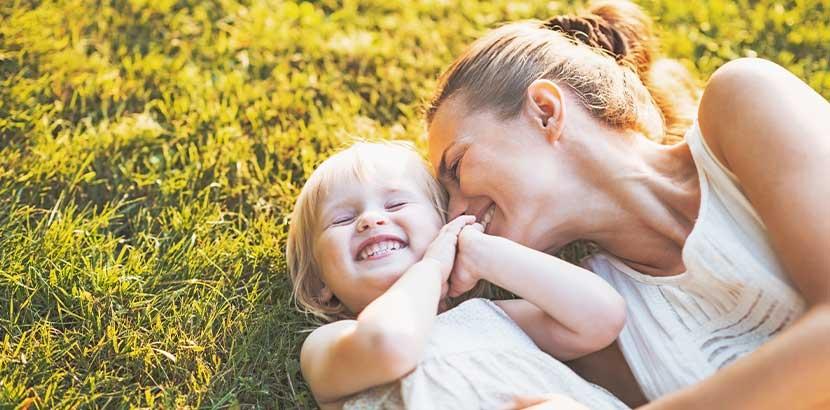 Junge Frau mit kleiner Tochter lachend im Gras. Gebärmutterhalskrebs Symptome.