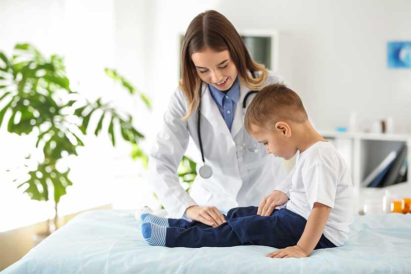 Junge Kinderorthopädin, die das Bein eines kleinen Jungen untersucht, der auf einer Behandlungsliege sitzt.