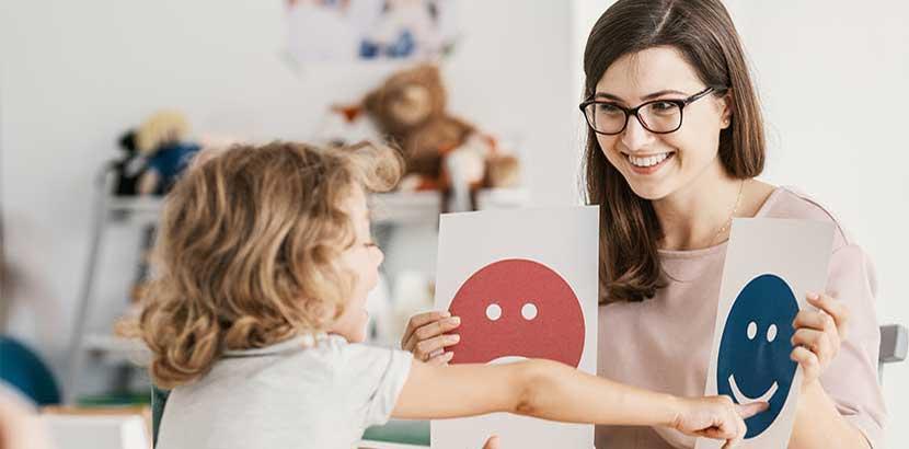 Junge dunkelhaarige Kinderpsychologin, die mit einem kleinen Mädchen arbeitet.