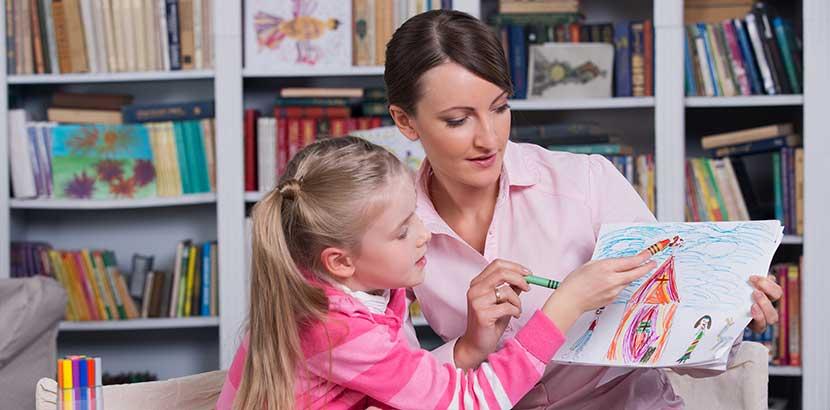 Junge dunkelhaarige Kindertherapeutin, die mit einem kleinen blonden Mädchen arbeitet.