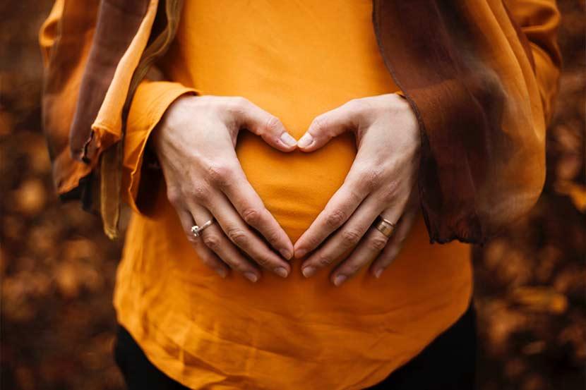 Mutter-Kind-Pass: Eine schwagere Frau hält sich die Hände über ihrem Schwangerschaftsbauch.