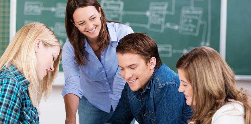 Nachhilfe Englisch: eine Frau gibt drei Schülern Englisch-Nachhilfe in Wien