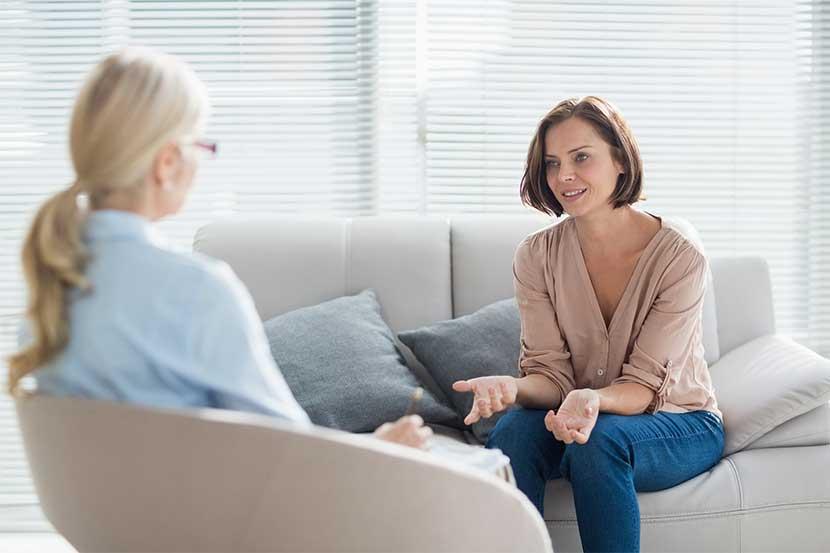 Blonde Psychotherapeutin, die mit einer jungen dunkelhaarigen Patientin spricht.