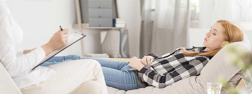 Junge blonde Klientin, die bei der Psychotherapie Wien auf einer Liege liegt und von einer Psychotherapeutin betreut wird.