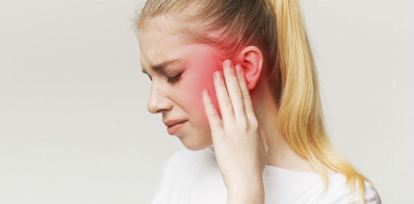 Eine junge Frau leidet unter Tinnitus.