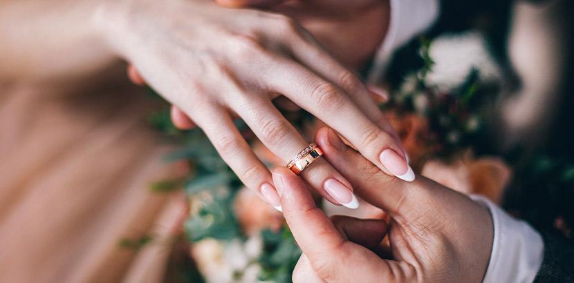 Trauringe - welche Hand? Ein Mann steckt einer Frau bei der Hochzeit den Ehering an den Ringfinger der rechten Hand.