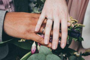 Trauringe an den Händen eines Hochzeitspaares