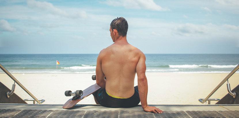 Trockene Haut durch Sonne: Ein Mann sitzt mit seinem Skateboard am Strand.