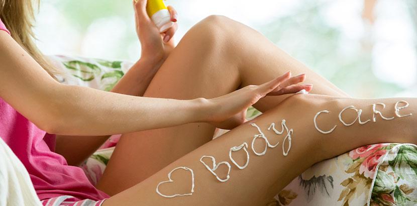 Trockene Haut Bilder: eine Frau cremt ihre Beine ein