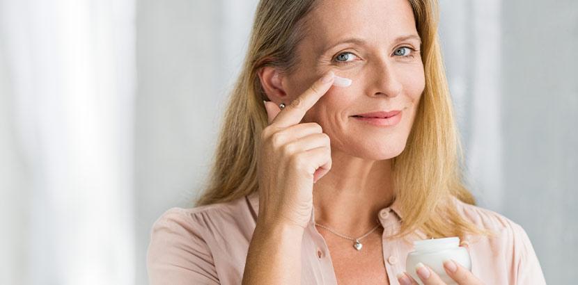 Eine Frau streicht Creme auf ihre reife, trockene Haut
