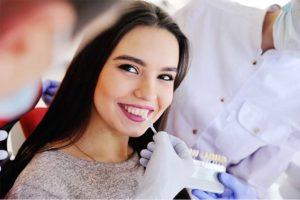 Junge hübsche dunkelhaarige Patientin beim Zahnarzt, die sich Veneers anpassen und einsetzen lässt.