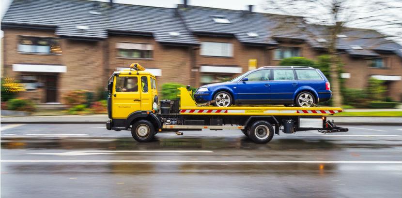 Ein gelbes Abschleppfahrzeug transportiert einen PKW.