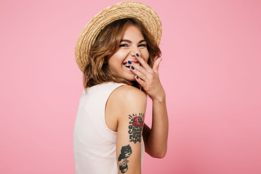 Close up portrait of a young pretty woman in summer hat laughing and covering her mouth with hand isolated over pink background