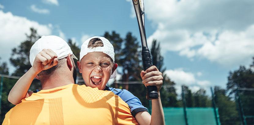 Kleiner Junge mit seinem Vater beim Tennisspielen. Legasthenie und LRS.