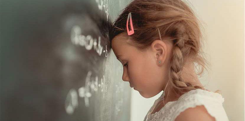 Kleines Mädchen mit LRS oder Legasthenie, das in der Schule verzweifelt den Kopf an die Tafel lehnt.