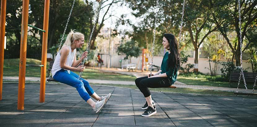 Liebeskummer überwinden: Freundinnen sitzen auf Schaukeln und reden miteinander