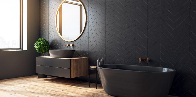 Wohnidee: Bad mit hellen Fliesen in Holzoptik (Eiche), schwarzen Wandfliesen und schwarzer Badewanne. Dazu kombiniert wird ein goldener, runder Spiegel an der Wand.
