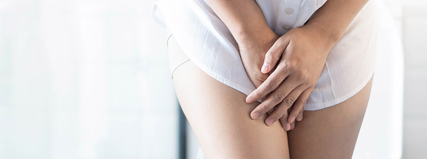Nahaufnahme einer Frau, die die Hände im Schritt verschränkt. Inkontinenz, Harninkontinenz.