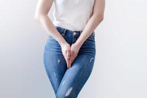 Unterkörper einer jungen Frau, die die Hände vor dem Schritt verschränkt. Inkontinenz, Harninkontinenz.